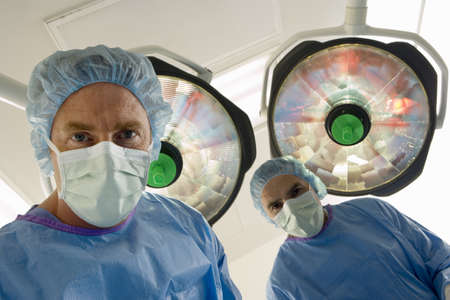 personal perspective: Surgeons in surgical masks standing in operating theatre, low angle view, personal perspective LANG_EVOIMAGES
