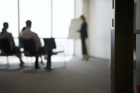 toils: Businesswoman giving presentation to colleagues in conference room, focus on doorway in foreground LANG_EVOIMAGES