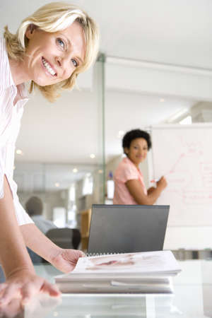 toils: Two businesswomen in meeting room, one looking at book on table, one using flipchart, smiling, portrait (differential focus) LANG_EVOIMAGES