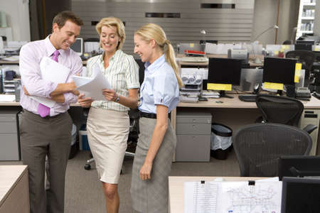 toiling: Businesswoman showing paperwork to colleagues in office, smiling, elevated view LANG_EVOIMAGES