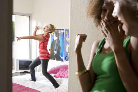 waistup: Two teenage girls (15-17) laughing at friend singing in bedroom LANG_EVOIMAGES