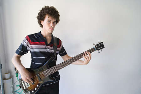 western european ethnicity: Teenage boy (16-18) playing electric guitar indoors, portrait
