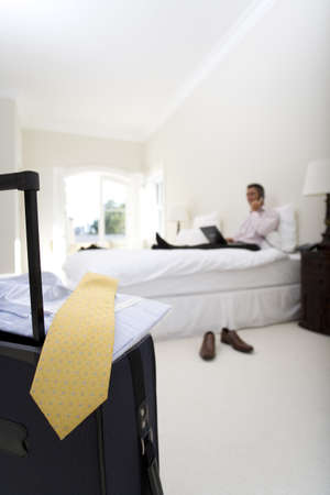 toiling: Mature businessman using laptop and mobile phone on bed, suitcase in foreground