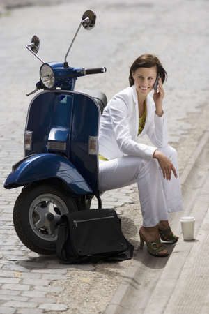 kerb: Woman sitting by roadside beside scooter, using mobile phone, smiling, disposable cup on kerb