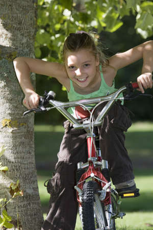 appreciating: Girl (7-9) sitting on bicycle beside tree in garden, leaning forwards, smiling, front view, portrait