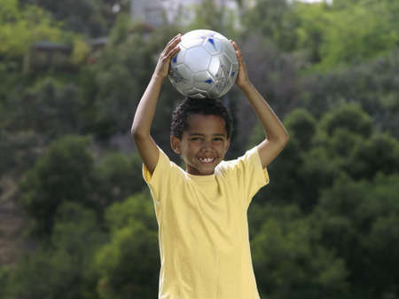 pleas: Boy (7-9) standing in park with soccer ball above head, smiling, front view, portrait