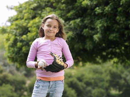 guante de beisbol: Chica (7-9) que se coloca en el parque con el béisbol y el guante, sonriendo, vista frontal, retrato LANG_EVOIMAGES