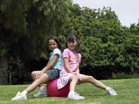 relishing: Two girls (7-9) sitting on pink space hopper in park, smiling, side view, portrait