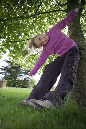 leant: Girl (7-9) wearing purple top and combat trousers, swinging from branch in garden, arms outstretched, head cocked, smiling, portrait, low angle view