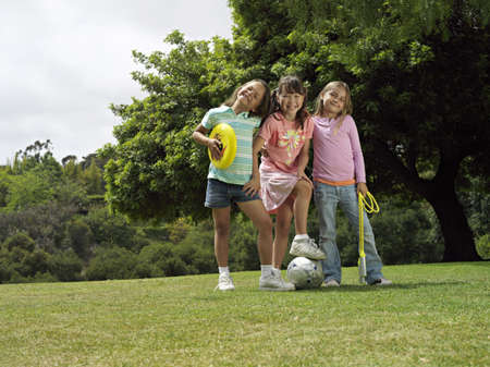 western european ethnicity: Three girls (7-9) standing on grass in park with frisbee, soccer ball and skipping rope, portrait