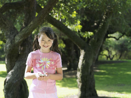 waistup: Girl (7-9) standing in park near trees, listening to MP3 player, smiling, front view, portrait LANG_EVOIMAGES
