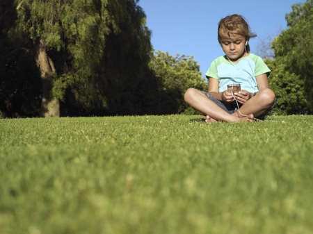 western european ethnicity: Girl (6-8) sitting on grass in park, listening to MP3 player, front view, surface level