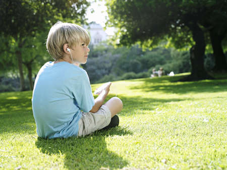 appreciating: Blonde boy (7-9) sitting on grass in park, listening to MP3 player, side view LANG_EVOIMAGES