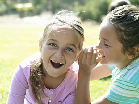 western european ethnicity: Girl (7-9) whispering in friends ear, second girl gasping, close-up
