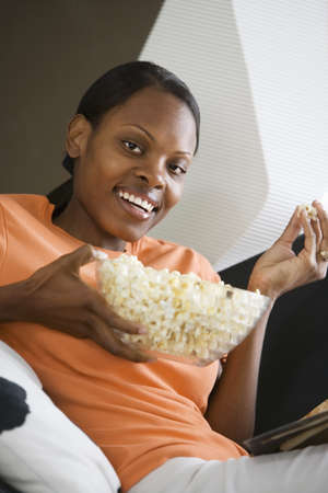 l nutrient: Woman relaxing at home, eating popcorn, smiling, side view, close-up, portrait (tilt)