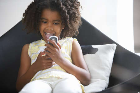 gratifying: Girl (8-10) sitting in chair at home, reading text message on mobile phone, mouth open, front view