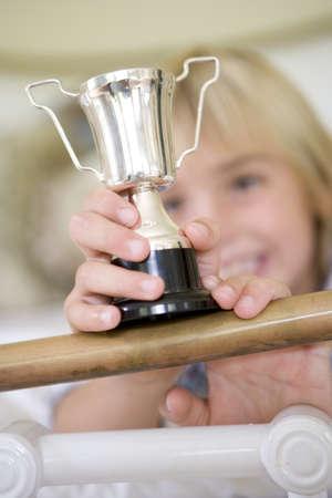 gratifying: Girl (6-8) holding trophy, smiling, focus on trophy