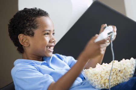 waistup: Boy (4-6) playing with games console at home, full bowl of popcorn in lap, smiling, close-up, side view