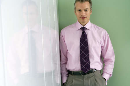 toiling: Businessman standing in corner of office, hands in pockets, smiling, portrait, reflection in glass LANG_EVOIMAGES