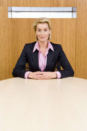 toils: Businesswoman at conference table, hands clasped, portrait