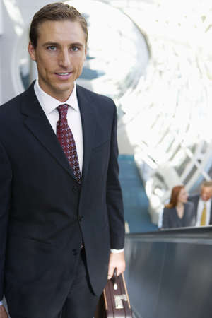 elevated view: Businessman standing on escalator, carrying briefcase, smiling, portrait, elevated view