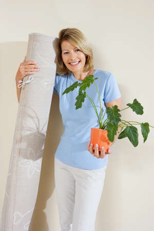western slope: Senior woman holding pot plant and rolled up carpet, moving house, smiling, front view, portrait LANG_EVOIMAGES