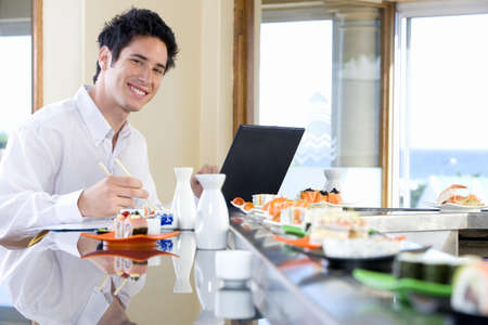 western european ethnicity: Young man eating in sushi bar, smiling, portrait