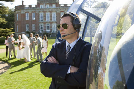 lavishly: Helicopter pilot in sunglasses by helicopter, wedding party in background LANG_EVOIMAGES