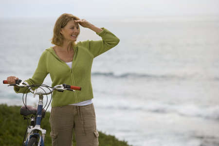 fema: Mature woman with bicycle by sea, looking into distance