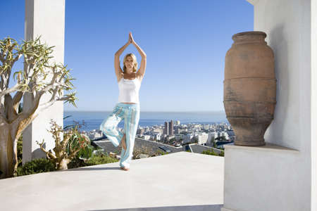 lavishly: Young woman standing on balcony in tree pose yoga stance, portrait LANG_EVOIMAGES