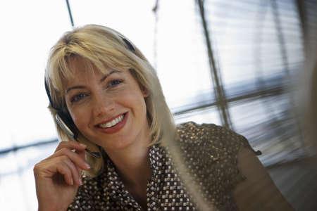 toils: Blonde businesswoman wearing telephone headset, smiling, close-up, portrait (tilt)