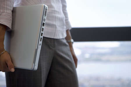toils: Businesswoman standing beside window, carrying laptop underarm, close-up, side view, mid-section LANG_EVOIMAGES