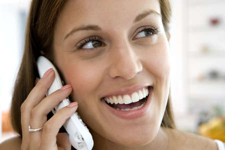 western european ethnicity: Young woman using telephone, smiling, close-up
