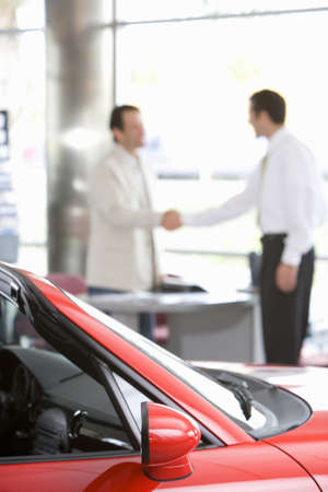 showroom: Salesman shaking hands with male customer in car showroom, focus on red convertible in foreground