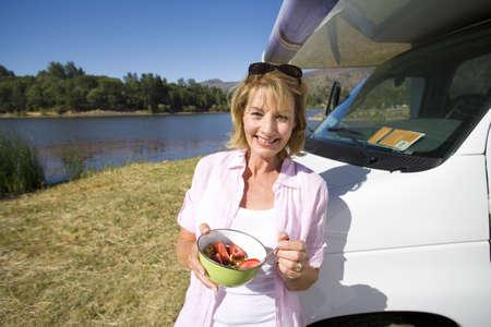 waistup: Mujer madura con un taz�n de desayuno por la casa rodante y el lago, sonriente, retrato LANG_EVOIMAGES