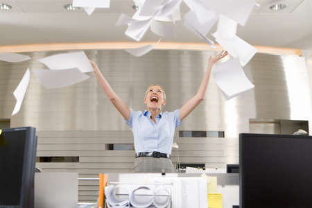 toils: Businesswoman throwing paper up in office, arms raised, smiling, low angle view LANG_EVOIMAGES