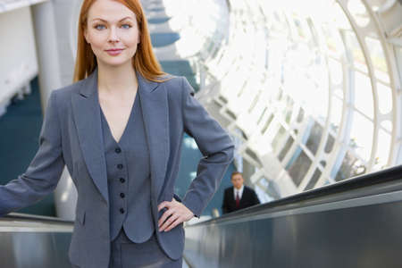 elevated view: Businesswoman standing on escalator, hand on hip, smiling, front view, portrait, elevated view