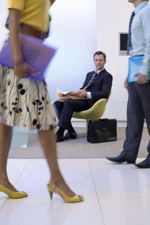 toils: Businessman and woman walking in foyer by businessman in chair with newspaper, low section (blurred motion)
