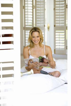 sitt: Young woman reading in underwear by shutters, smiling, portrait