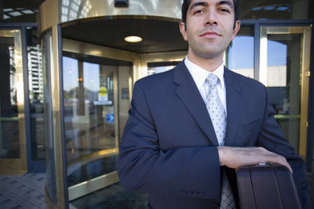 western european ethnicity: Businessman standing in front of revolving door, carrying briefcase, smiling, front view, portrait