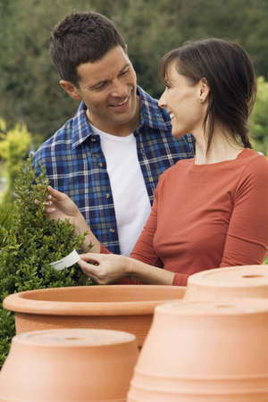 western european ethnicity: Couple shopping for plant pots in garden centre, woman holding price tag, smiling LANG_EVOIMAGES