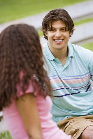 western european ethnicity: Teenage couple (17-19) talking in park, focus on teenage boy in background LANG_EVOIMAGES
