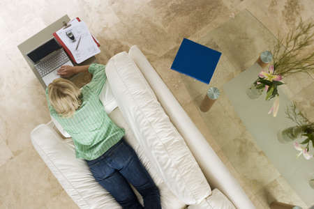toils: Woman lying on sofa at home, using laptop resting on coffee table, overhead view LANG_EVOIMAGES