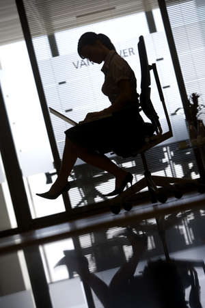 toils: Silhouette of businesswoman sitting in office chair, using laptop, profile, surface level (tilt)