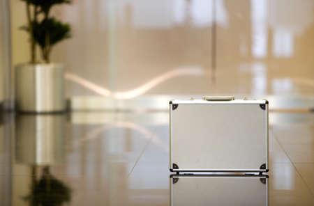 shiny floor: Reflection of silver briefcase on shiny lobby floor