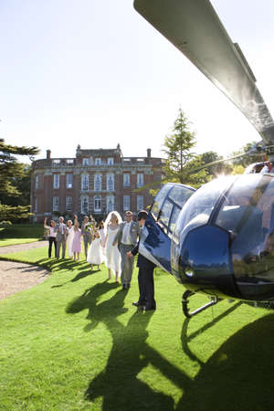 lavishly: Wedding party watching bride and groom walking towards helicopter (lens flare)