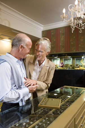 gentleman's: Mature couple in jewelery shop, woman trying on ring, smiling