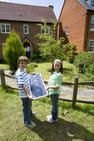 appreciating: Brother and sister (6-10) with solar panel by house, portrait