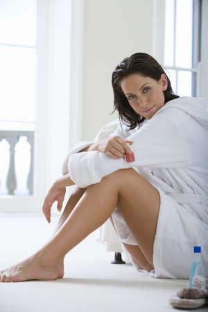 western european ethnicity: Young woman wearing white bath robe, sitting on floor, portrait