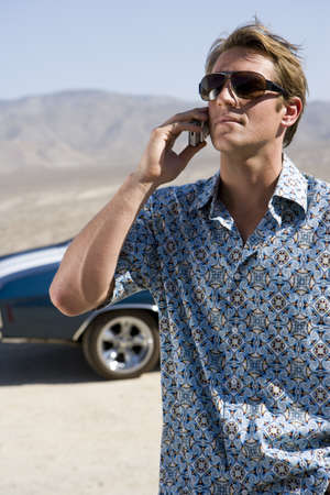waistup: Young man in sunglasses using mobile phone by car in desert LANG_EVOIMAGES